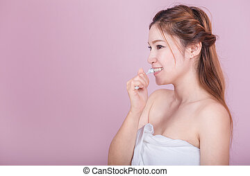 happy beautiful woman brushing her teeth on pink background