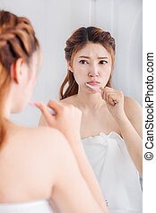unhappy woman in bath towel brushing teeth with mirror in...