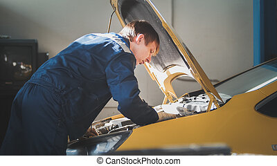 A mechanic checks the electrical in the hood of the yellow...