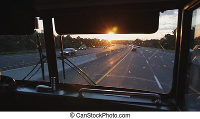 Busride Sunset - Riding at the front of a greyhound bus on...