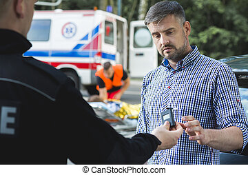Policeman examining sobriety of scared driver after car...