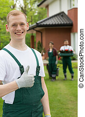 Smiling gardener standing with the thumb up - Young smiling...