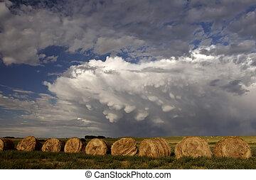 Storm clouds behind hay bales