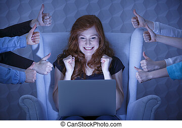 Excited girl with laptop - Excited girl using laptop at...
