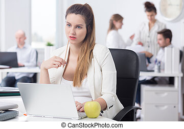 Distracted pregnant woman at work, sitting beside desk