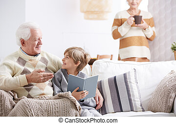 Grandson reading book with grandfather - Grandson reading...