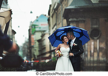 Groom kisses bride's forehead standing under the umbrella