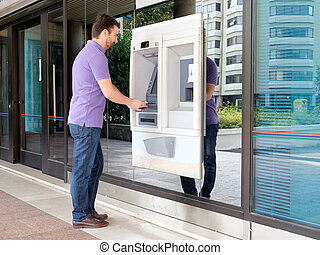 Man using his credit card in an atm for withdrawal - Man...