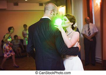 Green disco light shines over a dancing wedding couple