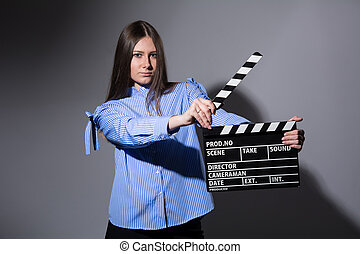 Close-up of a young women with movie clapper - Close-up of a...