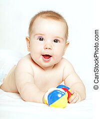 Happy child playing with ratte - baby, 5 months old