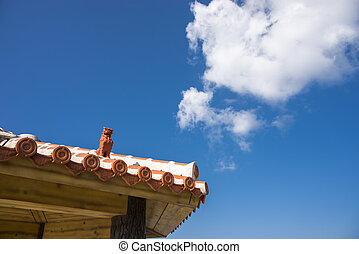 Tiled roof arbour on Shisa(Okinawan lion statues) under sky...