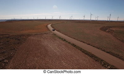 Following a black car in windmill farm, back light - Aerial...