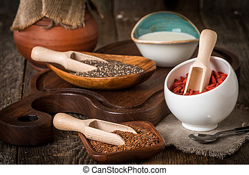 Seeds and goji in a wooden spoons