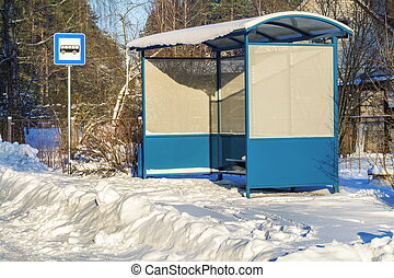 Bus shelter near snow covered road in winter