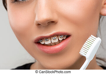 Beautiful young woman with teeth braces on gray with...
