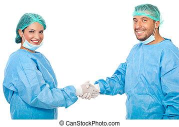 Surgeons team handshake - Two happy surgeons team shaking...