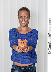 woman with piggy bank - a young woman holding a piggy bank...