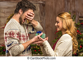 Woman giving christmas present to man