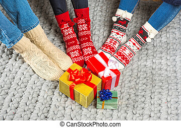 Legs in knitted socks and christmas presents - Human legs in...