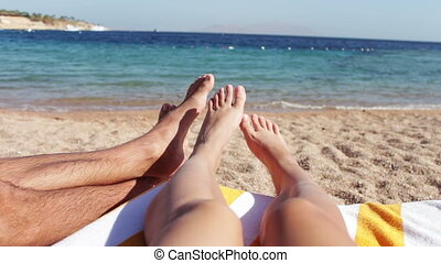 legs lie on a sun lounger on the beach - male and female...