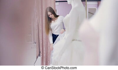 Young woman chooses a prom gown in shop - girl chooses a...