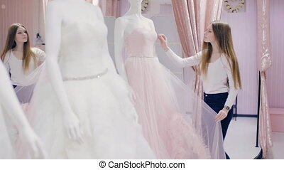 Young woman chooses a wedding dress in bridal shop - girl...