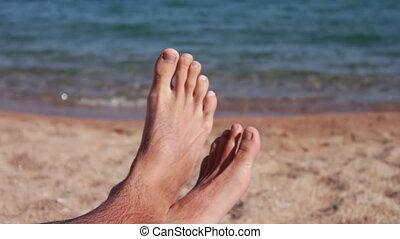 legs lie on a sun lounger on the beach - male legs lie on a...