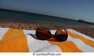 Sunglasses lying on a sun lounger in the background sea and...