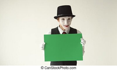 man mime holding a green billboard.