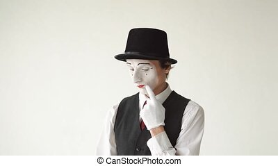 man mime stands on a white background and thinks.