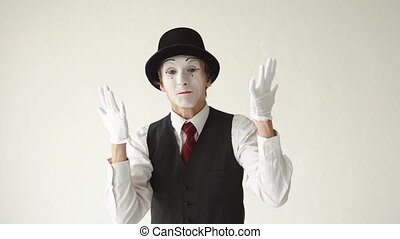 man mime standing on white background and swears, looking into the camera