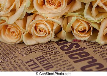 Many natural beige roses background on a newspaper