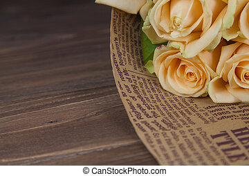 Many natural beige roses background on a wooden table, close up