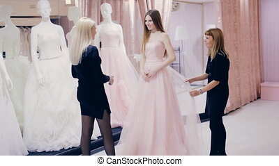 girl and consultants choose a wedding dress in a boutique -...