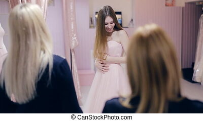 Young woman chooses a prom dress in a boutique
