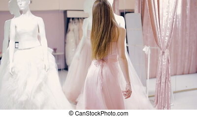 Pretty girl trying on prom gown in fitting room - Young...