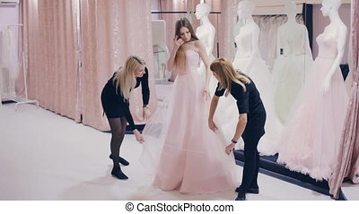 Pretty girl trying on wedding gown in fitting room -...