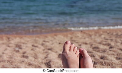 legs lie on a sun lounger on the beach - female legs lie on...
