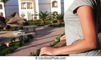 young woman standing on the balcony and stares into the...