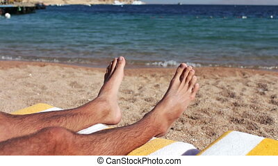 legs lie on a sun lounger on the beach - male legs lie on a...