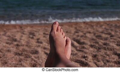 legs lie on a sun lounger on the beach - female legs lie on...