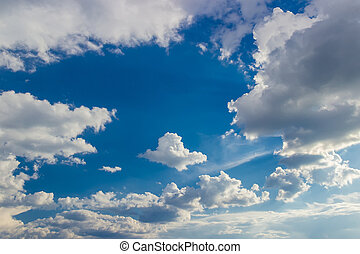 Background of the sky with cumulus clouds with sun rays from...