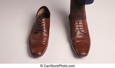 Man dresses brown shoes on white background and doing first...