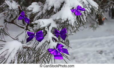 Decorated snowy forest tree with lilac ribbons