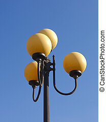 Street lamp in sunny day on a blue sky background