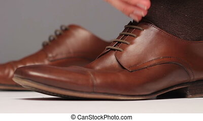 Man dresses brown shoes. side view - Man dresses brown shoes...