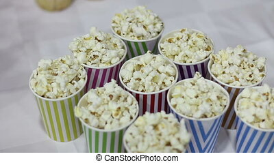 Popcorn in colored glasses at table