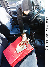 Burglar thief stealing smartphone and bag from car