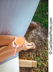 woman holding cocktail in the hammock - woman holding green...
